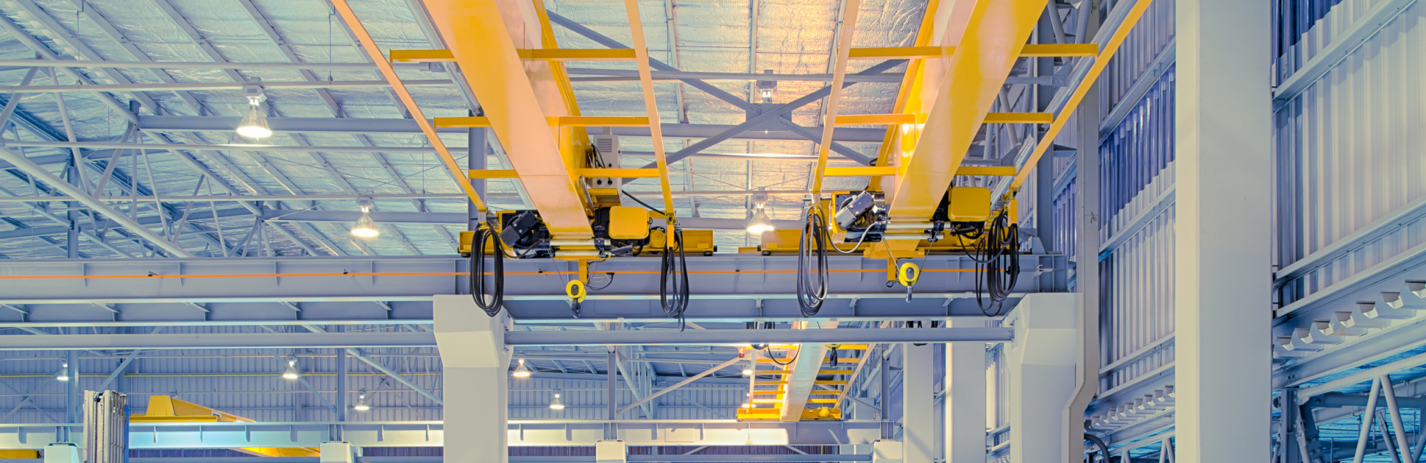 Overhead crane and concrete floor inside factory building for background.
